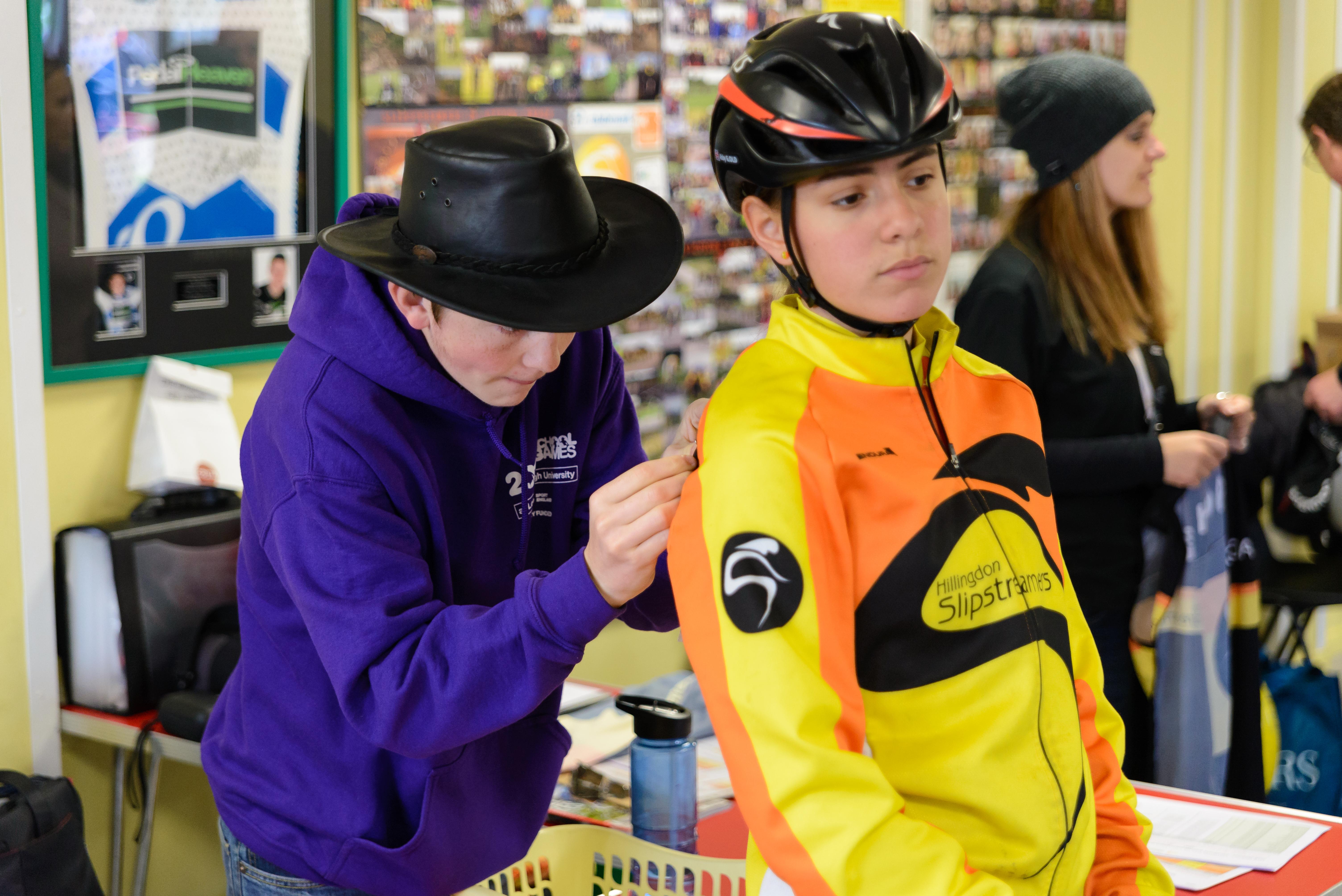 Volunteer pins a number onto a cyclist shirt